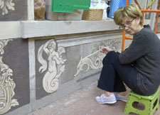 Lucia Popian is pictured restoring the sgraffito.