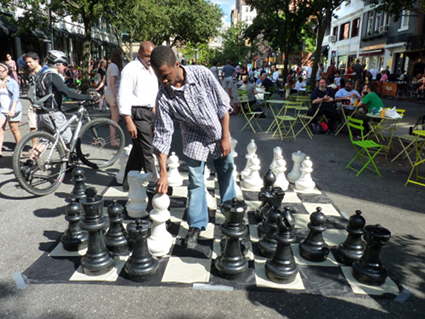 Asandoh Jones, instructor with New York Chess & Games (wearing a white shirt) plays a demonstration game of chess with teaching intern Phillip James. The Brooklyn Daily Eagle sponsors chess activities at the Montague Summer Space events.