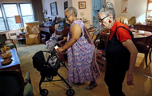 Carolyn Allen, left, a 69-year-old widow who has suffered two strokes, makes her way to the living room with roommate Marcia Rosenfeld, who owns the apartment Allen lives in New York
