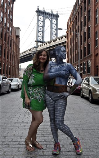 With the Manhattan Bridge behind them, artist Trina Merry, left, poses with model Jessica Mellow after painting her to blend into the bridge, in Brooklyn