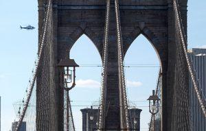 Helicopter flies over Brooklyn Bridge