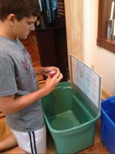 Basil Capetanakis prepares the collection bins he placed at various locations in Bay Ridge to gather toys, puzzles, school supplies and donations for Thursday's Child, a program that helps autistic children. The donation drive is the centerpiece of Basil's Eagle Scout project.