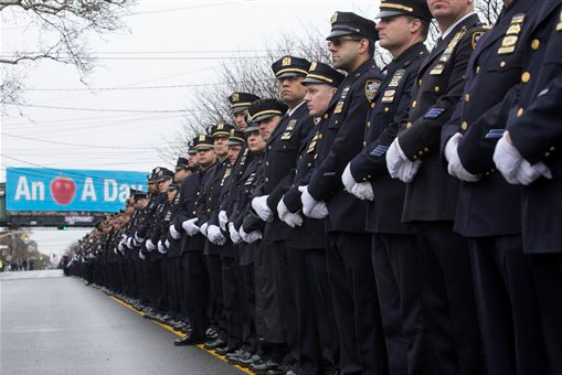 Police officers stand along the procession route during the funeral of New York Police Department Officer Wenjian Liu, on Sunday in Brooklyn. AP Photo/John Minchillo