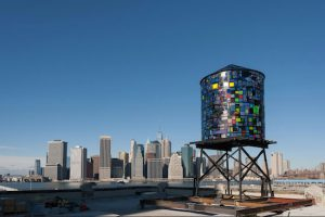 """Brooklyn artist Tom Fruin's solar-powered sculpture, """"Watertower 3: R.V. Ingersoll,"""" is stationed at the roof of 334 Furman St., near Pier 5, in Brooklyn Bridge Park. Fruin is one of several artists/cultural groups to be awarded below-market space in DUMBO by Two Trees Management Co. Photo by Julienne Schaer"""