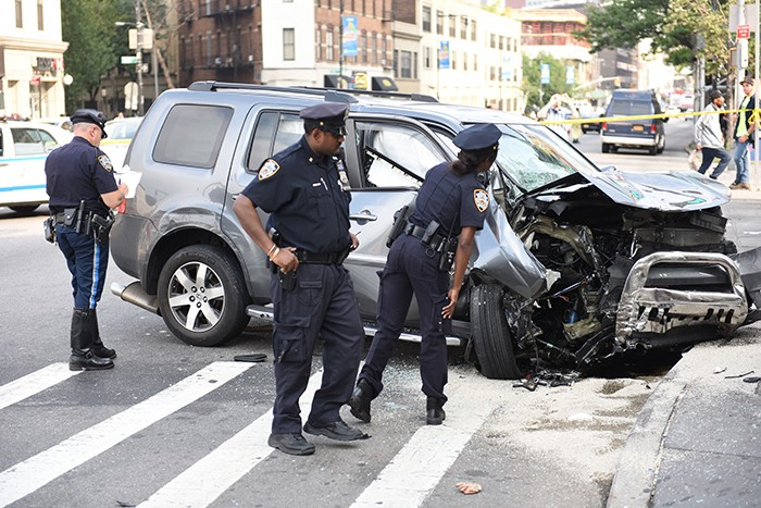 Police inspect the totaled SUV after it came to a rest in front of the LIRR station.