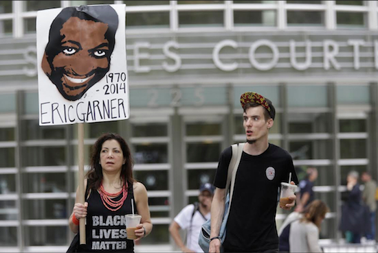 Demonstrators M.J. Williams, left, and Connor Hicks take part in a rally on Saturday outside the federal courthouse in Brooklyn to demand action in the fatal chokehold death of Eric Garner by a white police officer. AP Photos/Mary Altaffer