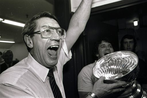 In this May 17, 1983, file photo, New York Islanders coach Al Arbour celebrates in the locker room as he holds the Stanley Cup after the Islanders won their fourth cup in a row, beating the Edmonton Oilers 4-2 to sweep the series at Nassau Coliseum. Arbour, who ranks as the NHL's second-most winningest coach, has died, team officials announced Friday. He was 82. The cause of death is unclear, though Arbor was battling a lengthy illness and had been living in Florida. AP Photo/Pool, File