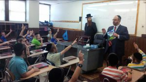 State Sen. Simcha Felder tells students in a yeshiva summer day camp program that it's important to wear a helmet while riding a bicycle. Photo courtesy of Felder's office
