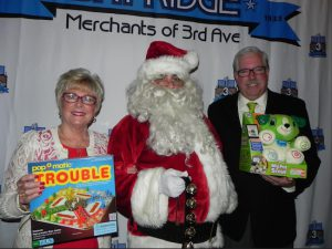 Santa Claus says he is pleased that so many toys were donated for the children of soldiers. Bob Howe, president of the Merchants of Third Avenue, and his wife Diane Howe, led the toy drive. Eagle photos by Paula Katinas