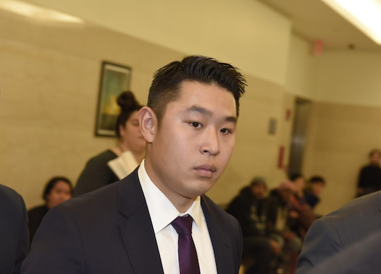 Accused NYPD Officer Peter Liang is stone-faced as he passes lines of activists and Gurley family supporters on his way to face charges in the East New York shooting. Eagle photos by Andy Katz