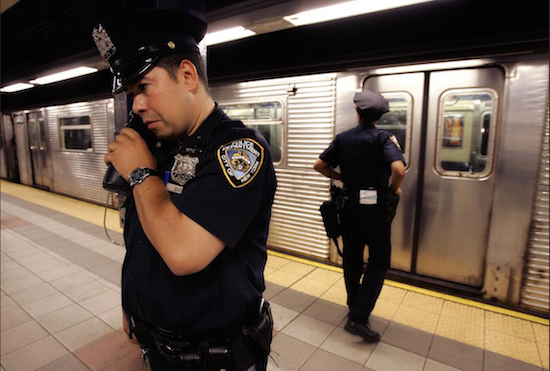In this July 8, 2005 file photo, NYPD Officer Frank Gotay listens to a message on his radio as his partner Yolanda Cortes waits for a subway car's doors to open while performing random checks along the platform at the 42nd Street station in Manhattan. New York City transit officers can finally communicate on their radios with police above ground. AP Photo/Julie Jacobson, File