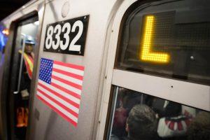 Riders stand inside an L-Train subway car. AP Photo/John Minchillo