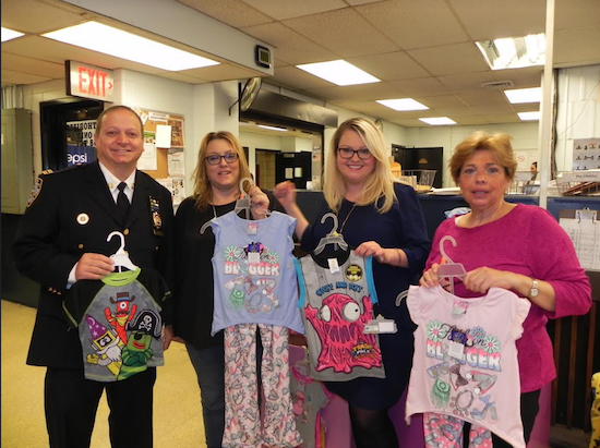 Capt. Joseph Hayward, commanding officer of the 68th Precinct, congratulates former 68th Precinct Community Council president Ilene Saco (second from left) on the success of the book and pajama donation drive that she organized with council members Kate Cucco (third from left) and Linda Lupia. Eagle photos by Paula Katinas
