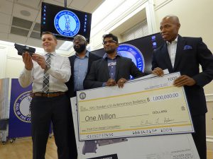 Autonomous Ballistics, a team from New York University Tandon School of Engineering, won the $1 million prize in a Smart Gun Design Competition funded by Borough President Eric Adams. Shown from left: Sy Cohen, mentor Professor Anthony Clarke, Ashwin Raj Kumar and Borough President Eric Adams. Photo by Mary Frost