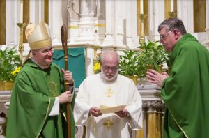 Bishop James Massa, at left, smiles as Deacon Edward Gaine (center, wearing white dalmatic) reads the official document of installation to the Rev. William G. Smith. Eagle photo by Francesca N. Tate