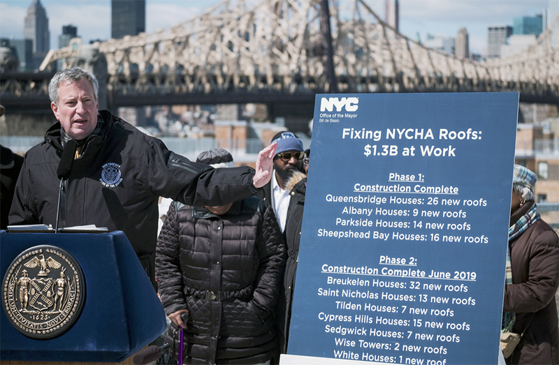 Mayor Bill de Blasio announced that leaky roofs have been fully replaced at 65 NYCHA buildings, at a press conference in Queens. He also mocked the timing of Gov. Andrew Cuomo's sudden interest in NYCHA repairs. Ed Reed/Mayoral Photography Office