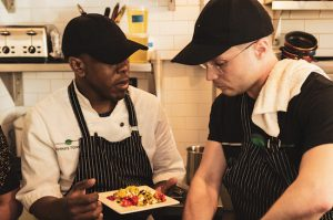 Emma's Torch, a nonprofit that empowers refugees, asylees and survivors of human trafficking through culinary education, recently opened at 345 Smith St. Shown: Culinary director Alexander Harris speaks with a student. Photos by Giada Randaccio Skouras Sweeny
