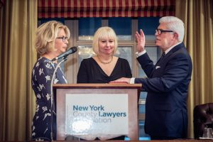 Michael Miller, the 121st president of the New York State Bar Association, is sworn in by NYS Chief Judge Janet DiFiore, as his wife Cindy looks on. Photo courtesy of the NYS Bar Association