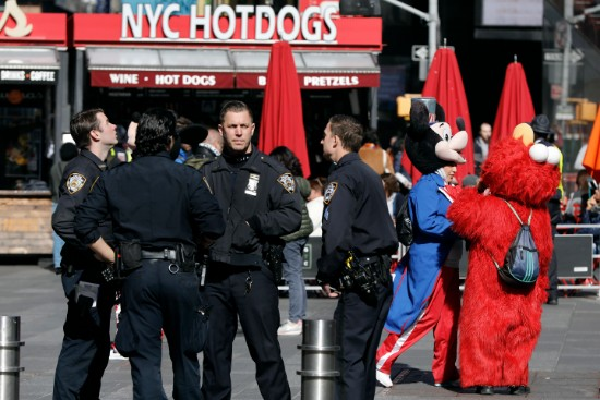 NYPD officers confer in Times Square on Friday. New reforms aimed at improving police interactions in New York City include requirements that officers hand out their business cards to people they stop and explain why law enforcement activity is taking place. AP Photo/Richard Drew