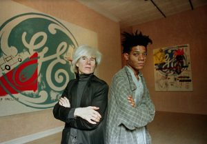 Jean-Michel Basquiat (at right), shown in this 1985 photo with fellow artist Andy Warhol, is buried in Green-Wood Cemetery. AP File Photo/Richard Drew