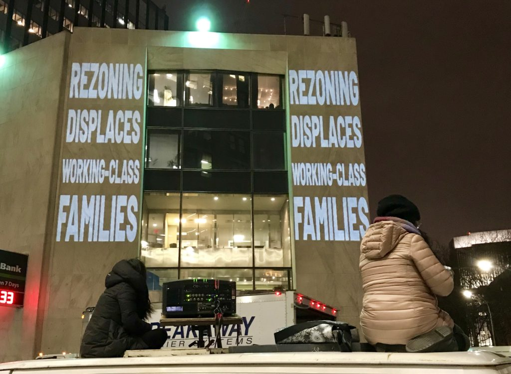 "Slogans like ""De Blasio, stop selling us out!"" and others were projected onto the facade of TD Bank in Brooklyn Heights Monday night. Activist groups G-REBLS and Mi Casa No Es Su Casa say a plan to rezone Bushwick fails to protect existing tenants, many people of color. Eagle photo by Mary Frost"