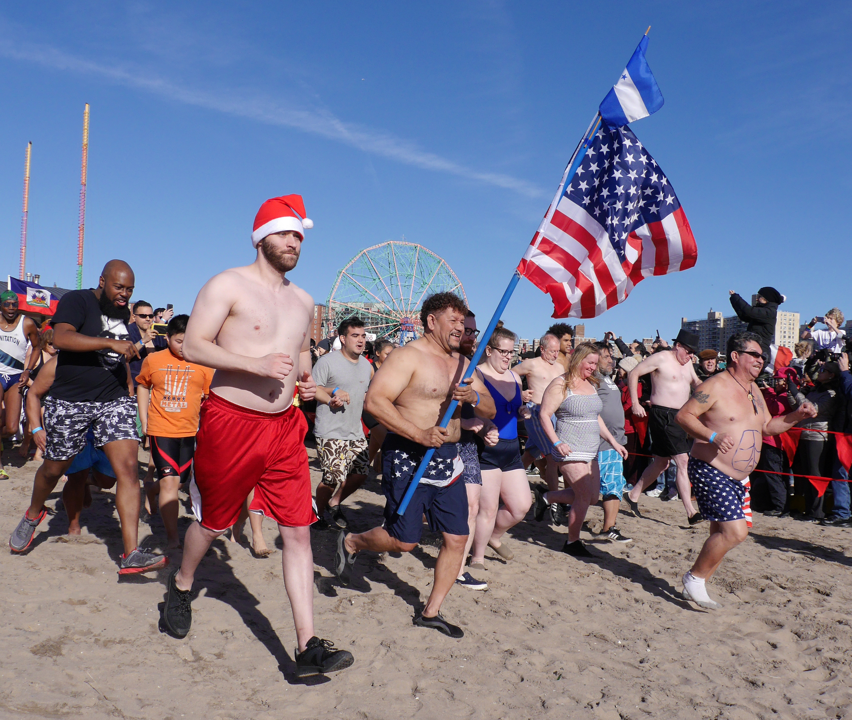 Roberto Velazquez proudly carries the American flag while attending the annual New Year's Day Polar Bear Plunge at Coney Island.
