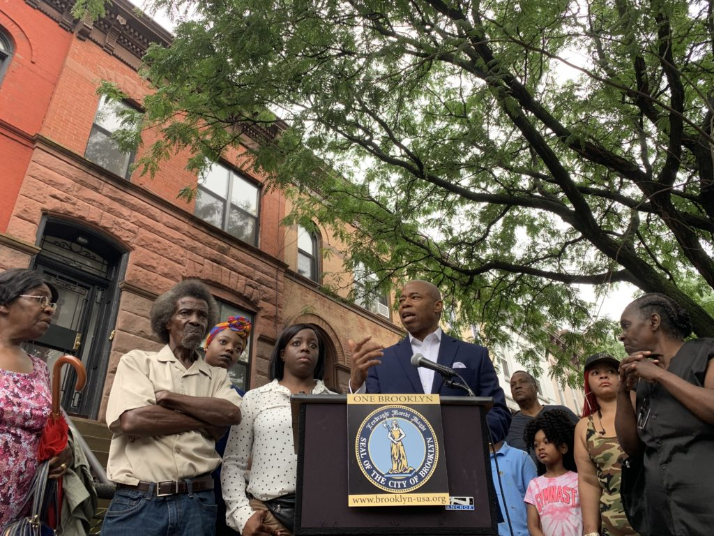 Brooklyn Borough President Eric Adams (center) announces a GoFundMe page to help a Bedstuy family with legal fees a day after they claimed they were the victims of deed theft. Eagle photo by Noah Goldberg