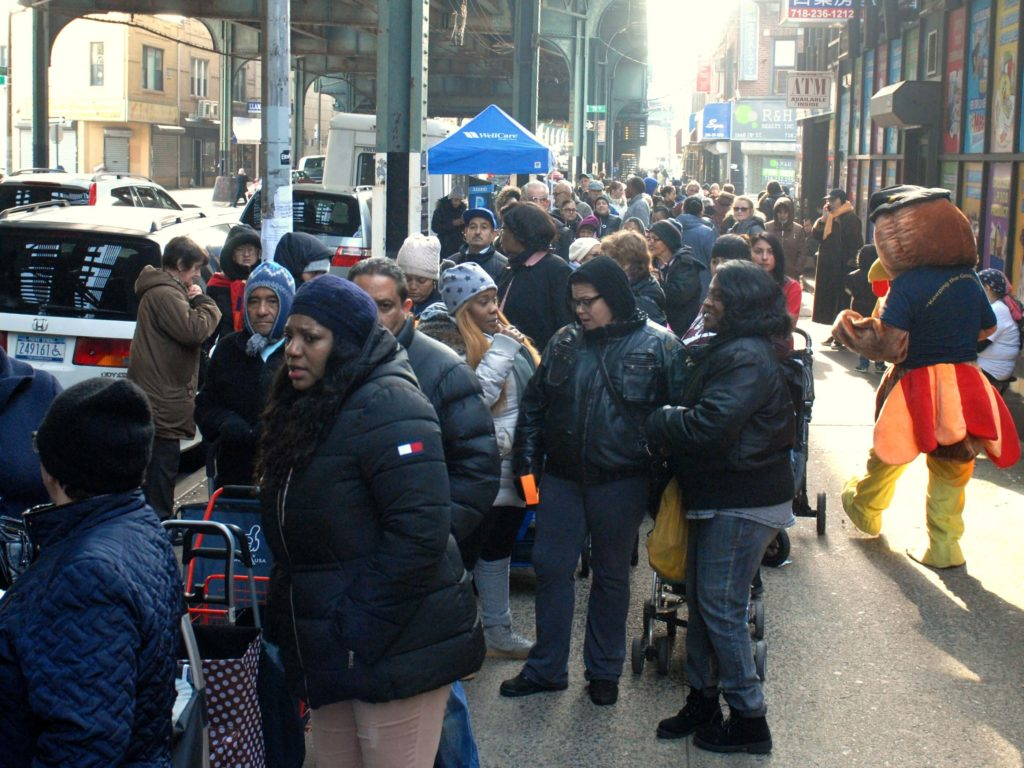Hundreds of people lined up on New Utrecht Avenue outside Reaching-Out for Thanksgiving turkeys last year. Eagle file photo by Arthur de Gaeta