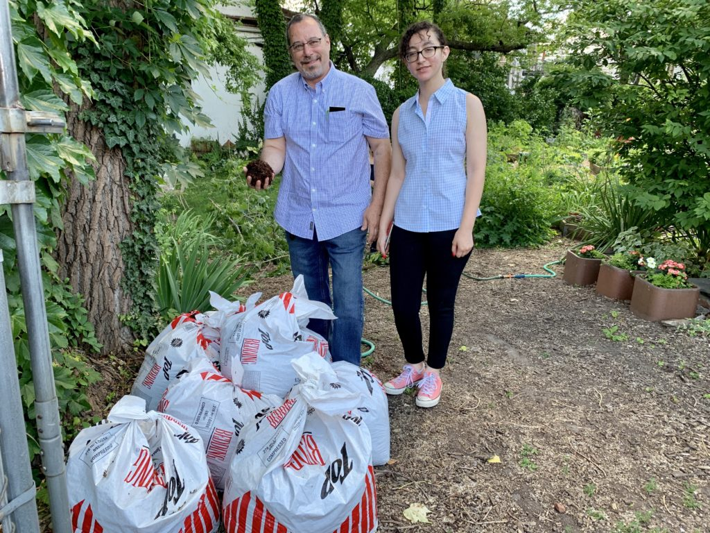 John Quadrozzi Jr., left, and his daughter Xiana rip open one of the first bags of composted manure delivered to Red Hook's Backyard Community Garden on Sunday. Xiana is a partner with her dad in Prospect Park Stable. Eagle photo by Mary Frost
