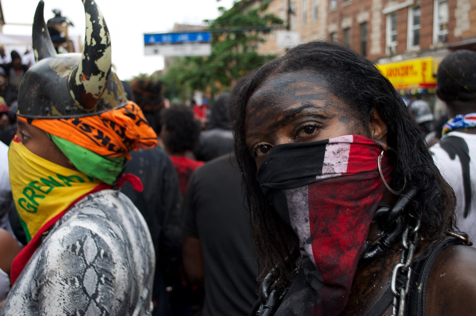 A marcher covered in motor oil wears the flag of Trinidad and Tobago around her face.