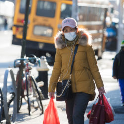 A woman wearing a medical mask does her shopping in Sunset Park, Brooklyn on Wednesday. Photo: Paul Frangipane/Brooklyn Eagle