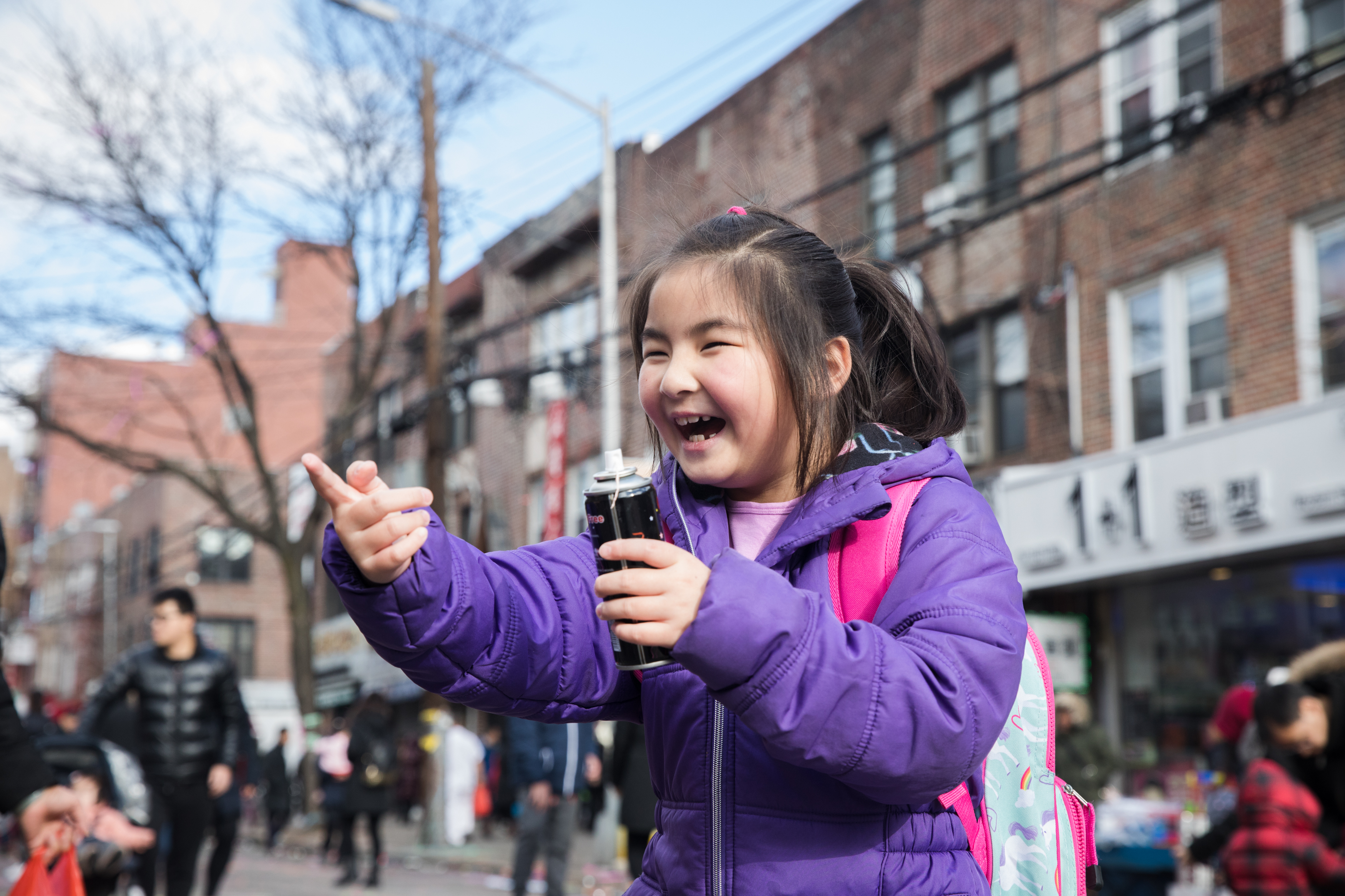 A little girl laughs as she sprays a relative with silly string.